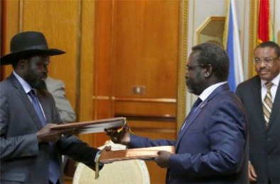Ethiopian prime minister Hailemariam Desalegn (R) looks on as South Sudan's Riek Machar (C) and Salva Kiir (L) exchange signed peace agreement documents in the Ethiopian capital, Addis Ababa, on 9 May 2014 (Photo: Reuters/Goran Tomasevic)