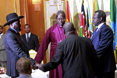 South Sudan's president, Salva Kiir (L), and rebel leader Riek Machar (R) shake hands and pray before signing a ceasefire agreement aimed at ending conflict in the country in the Ethiopian capital, Addis Ababa, on 9 May 2014 (Photo: AP/Elias Asmare)