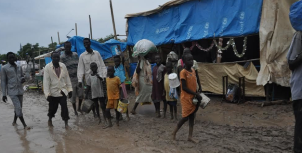 People walk along dirt roads that have been turned into streams of mud by the rains, in the UNMISS base in Malakal, South Sudan, where 19,000 people have sought shelter from months of fighting(Photo credits: Mugume Davis Rwakaringi)