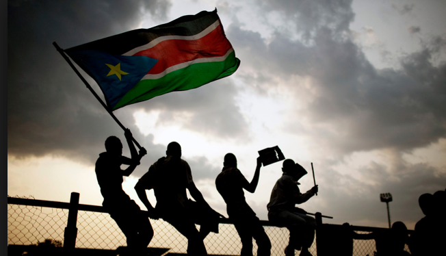 South Sudanese posting with a flag anticiparting the independent of South Sudan(photo: nyamilepedia)