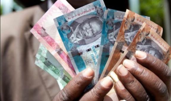 A man displaying South Sudanese pound...