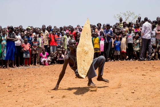 A Nuer man squatted in leather Shield demonstrating the warriors technique to prevent himself from getting hurt from his enemies (Photo/ Deng Nhial)