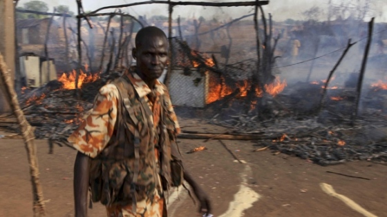 A policeman walks past the smouldering remains of a market in Rubkona near Bentiu in South Sudan on Monday. (Michael Onyiego/Associated Press)